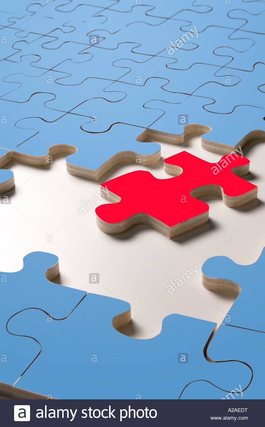 Close up of blank jigsaw puzzle with blue pieces, but with one red piece to be fitted in. - Stock Image