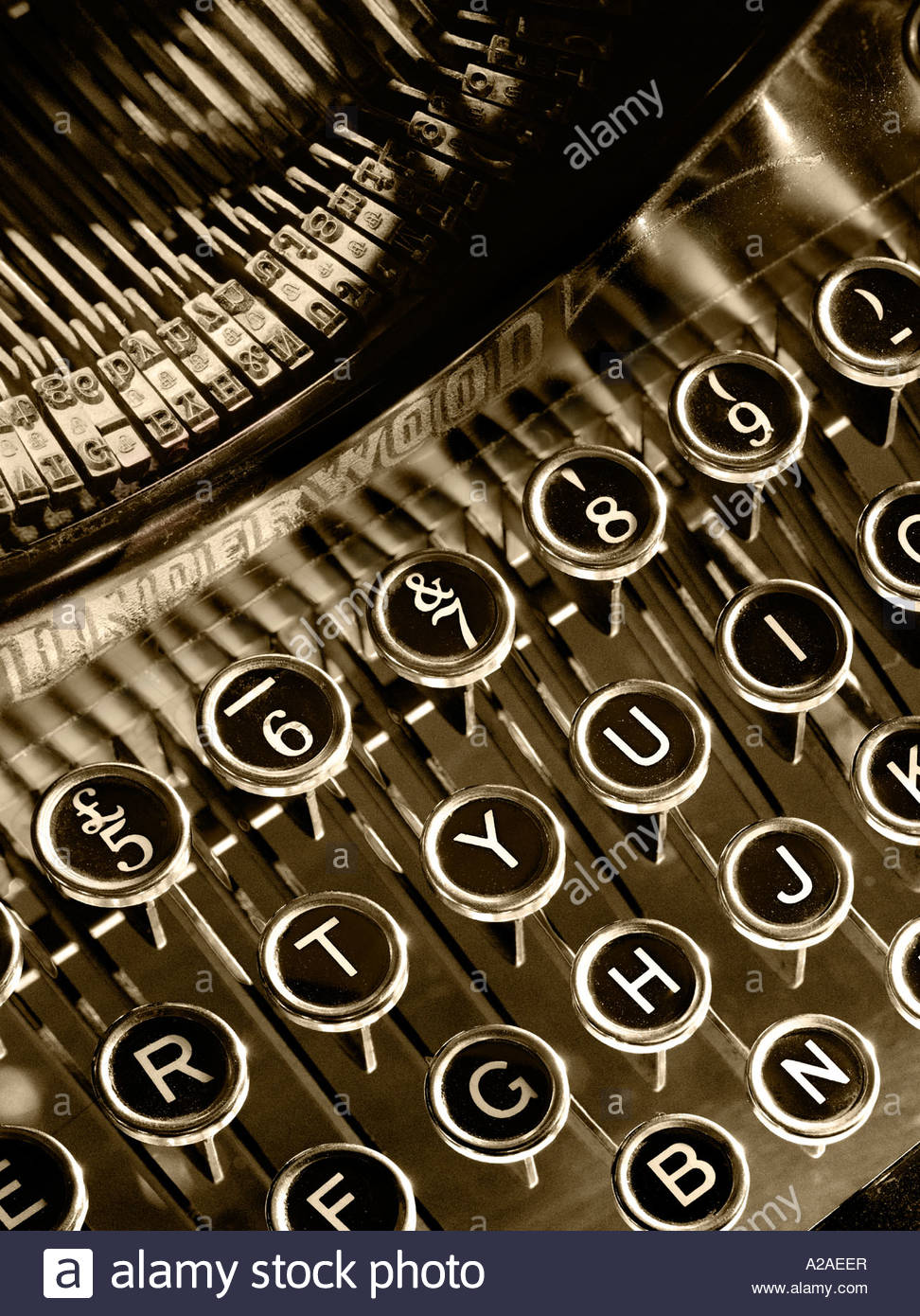 Close up of the keys on an old-fashioned mechanical typewriter, monochrome sepia treatment. - Stock Image