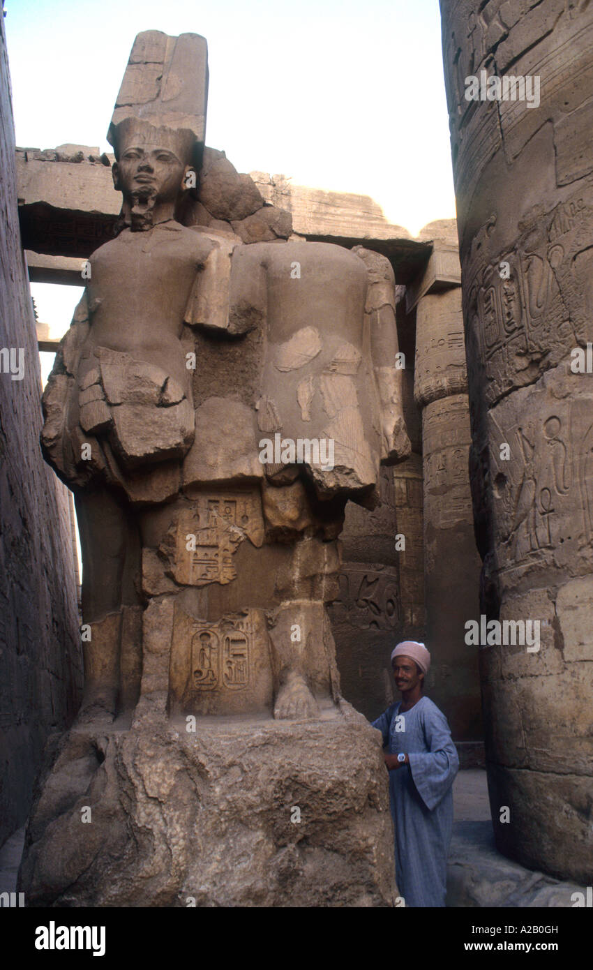 Egyptain Guide At The Base Of A Statue Depicting The Young Pharaoh Tutankhamun ,Inside The Karnack Temple Complex - Stock Image
