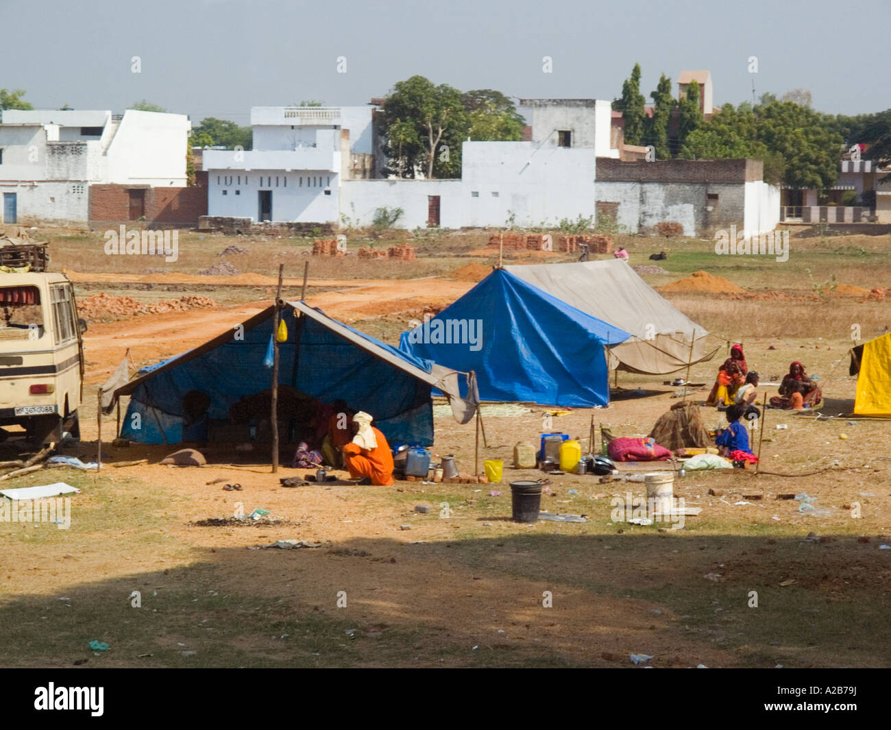 Campsite with makeshift tented homes with poor underclass people sitting on waste ground on town outskirts Madhya - Stock Image