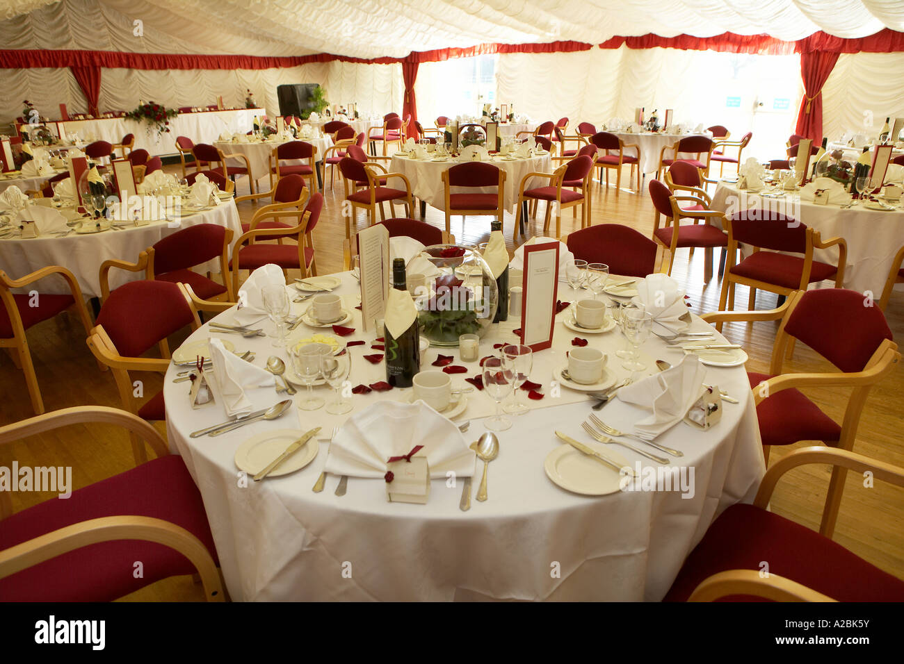 Tables set for a formal wedding reception inside a marquee Formal place settings at a wedding reception & Tables set for a formal wedding reception inside a marquee Formal ...