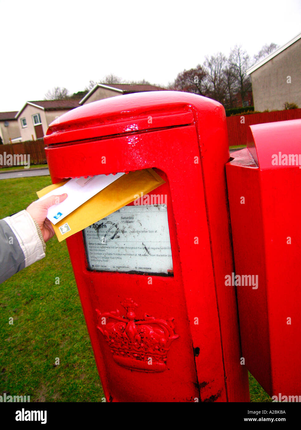 Close up of hand of person posting letters in red UK post box - Stock Image