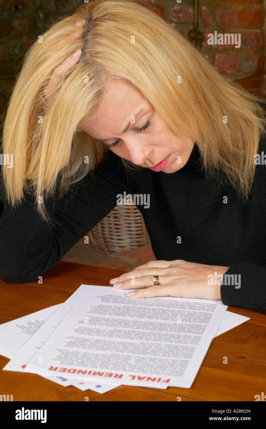 worried woman with bills and final reminders - Stock Image