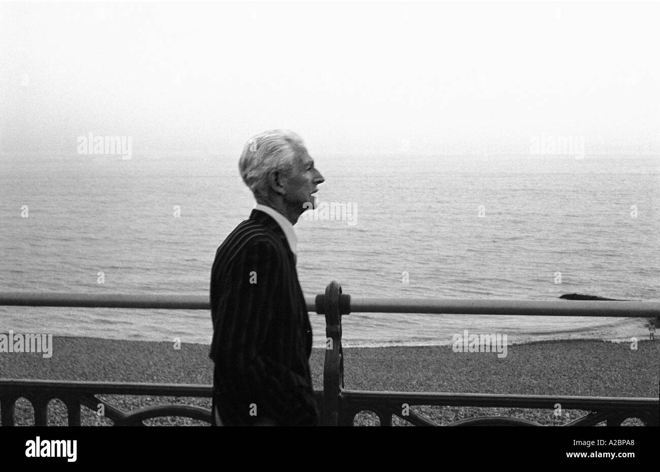 Retired man walking on sea front Brighton 1979 35mm b/w - Stock Image