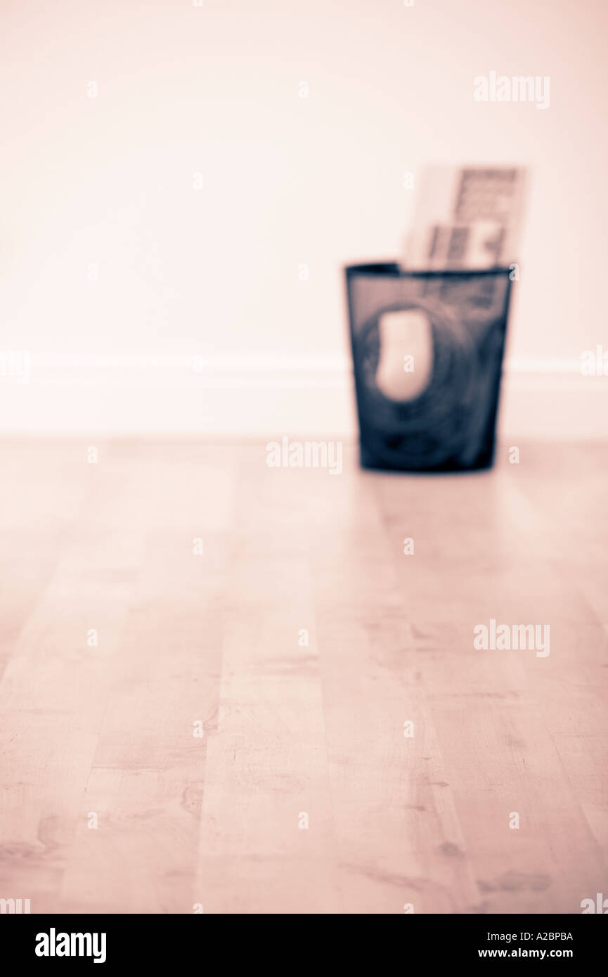 LITTER BIN FULL OF SCRAP COMPUTER EQUIPMENT ON WOOD OFFICE FLOOR Stock Photo