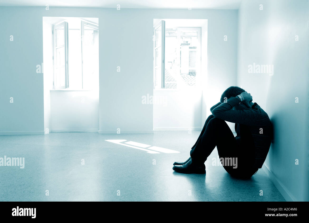 Alone man in an empty room - male with depression / mental illness / abuse / grief / mental health concept - Stock Image