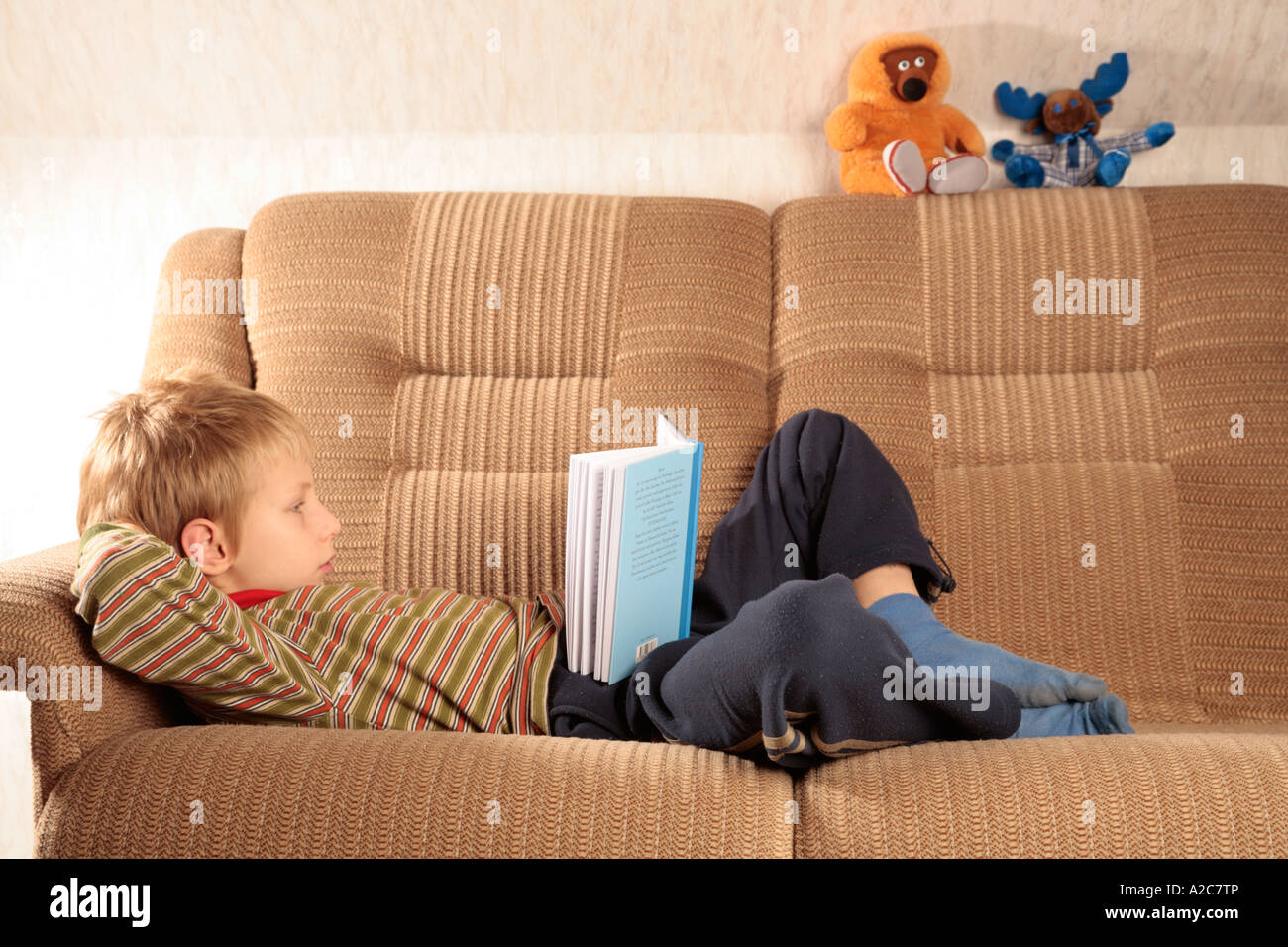 portrait of a young fair boy lying on a sofa and reading a book Stock Photo