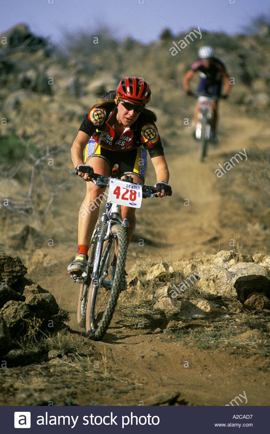 30 year old female Mountain Biker in front of male cyclist Arizona competing in 24 hour  endurance race Arizona - Stock Image