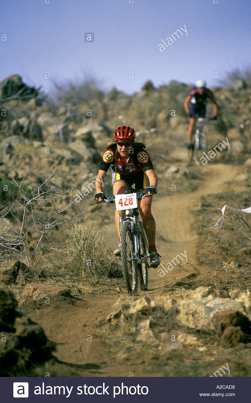 30 year old female Mountain Biker in front of male cyclist competing in 24 hour endurance  race in Arizona 24 hours of the Old - Stock Image