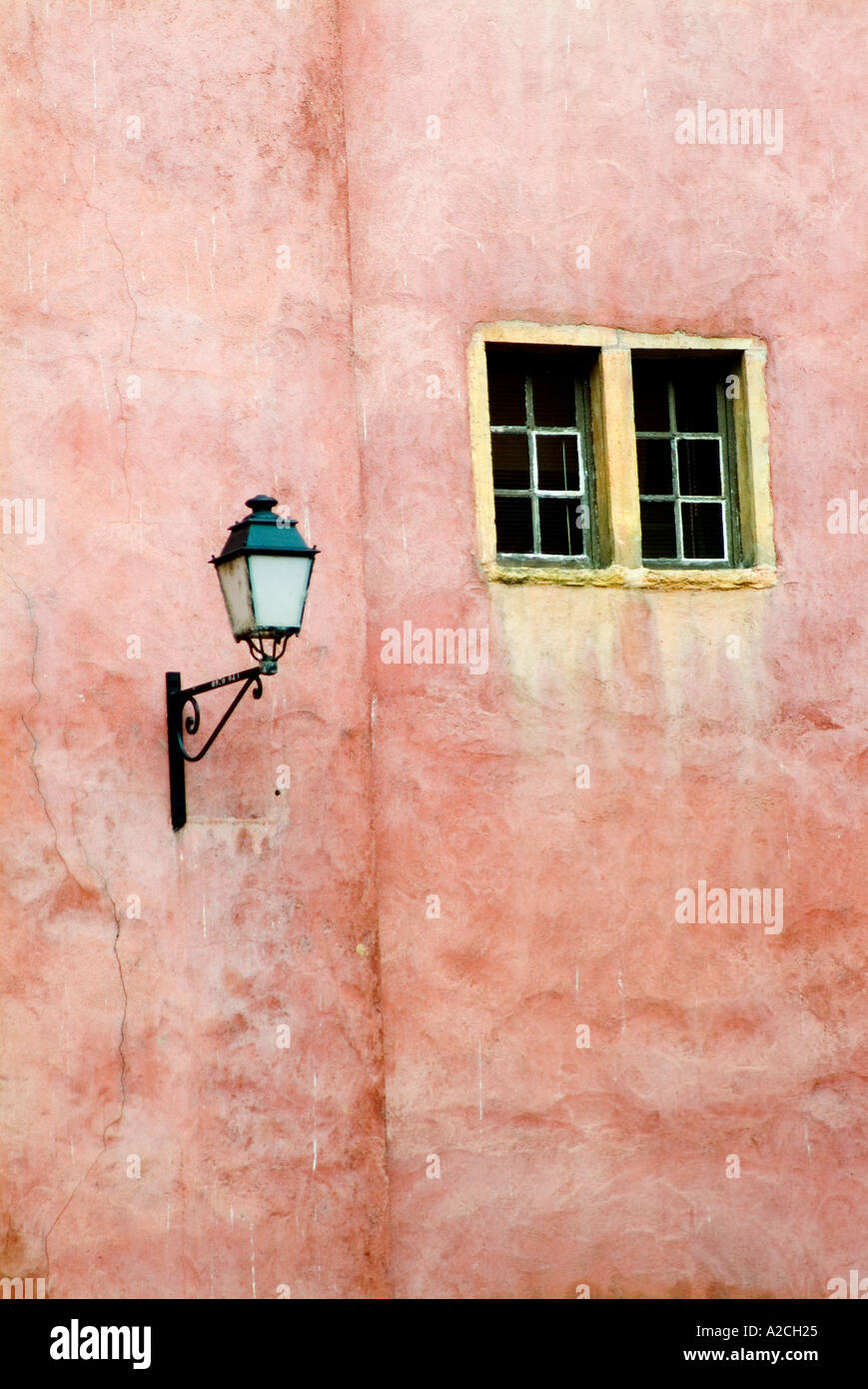 A red brick wall with a couple of windows and an old gas type light seperated by an indent in the wall Stock Photo