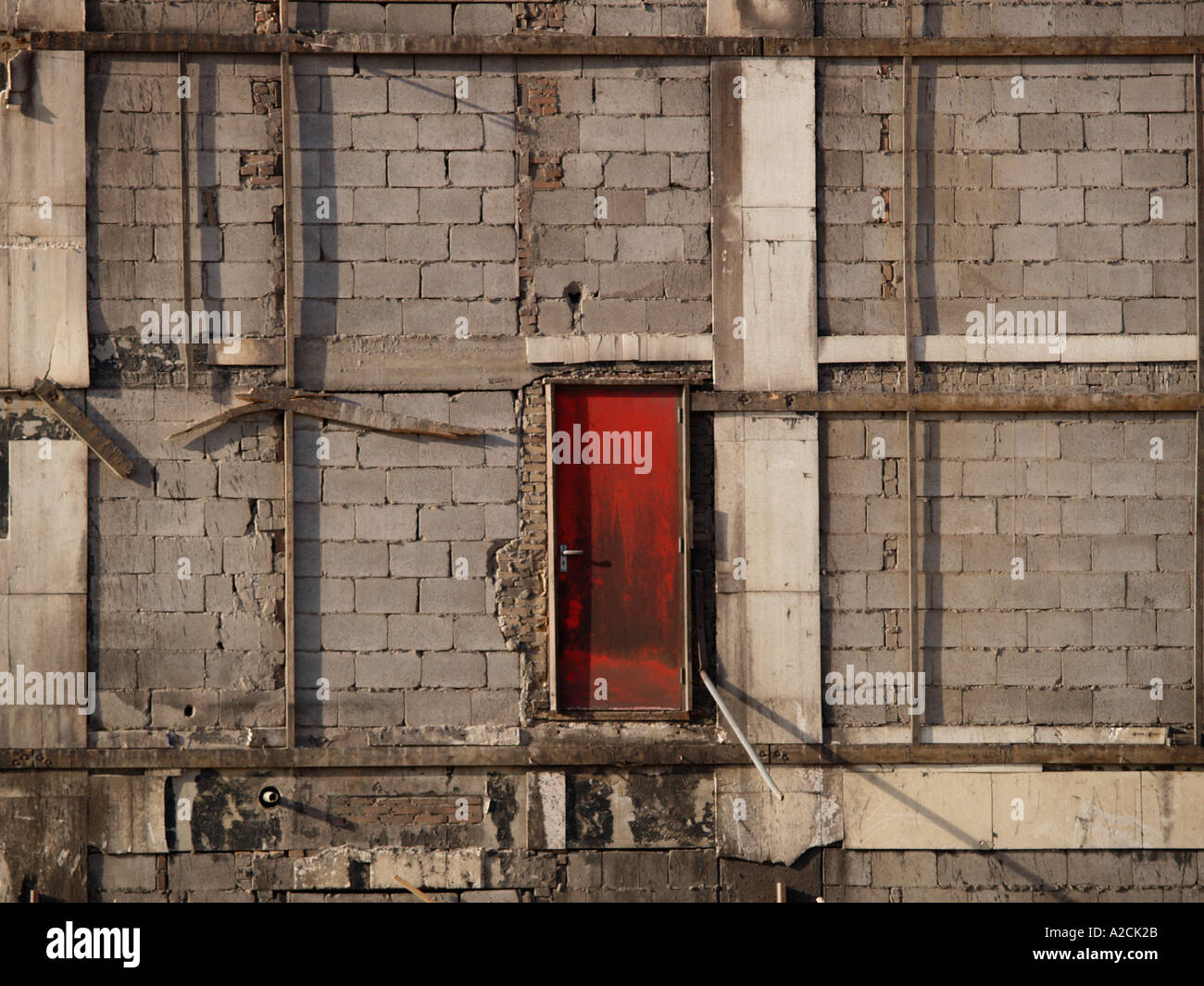 Grey wall with red door in building that is being demolished - Stock Image