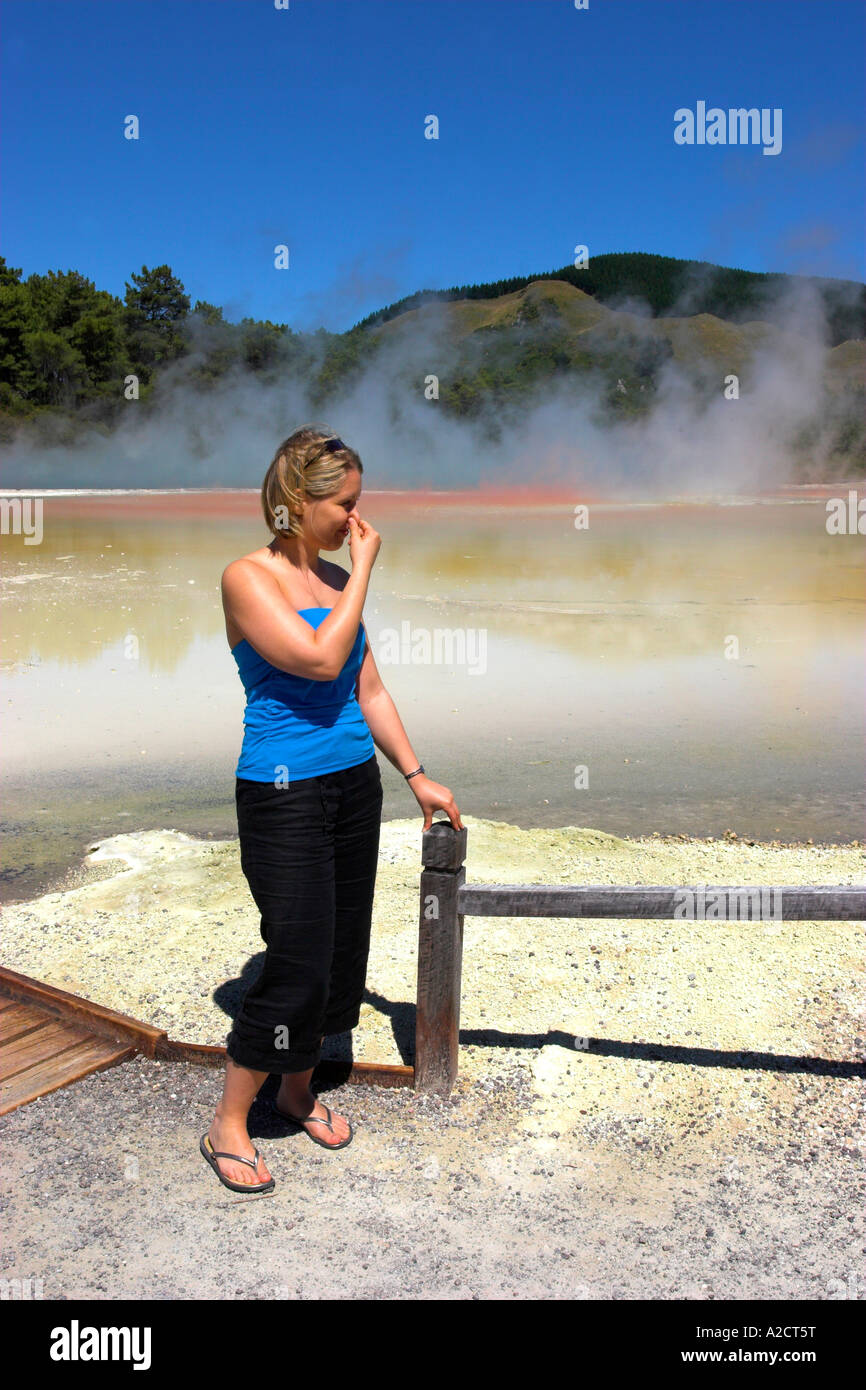 Young woman piching her nose due to the smell of sulphur at a volcanic pool at Wai O Tapu, New Zealand - Stock Image