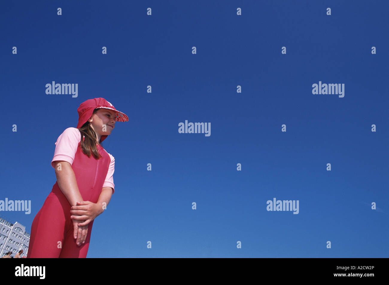 Ten year old girl plays pink uv sunsuit on Brighton Beach Sussex UK - Stock Image