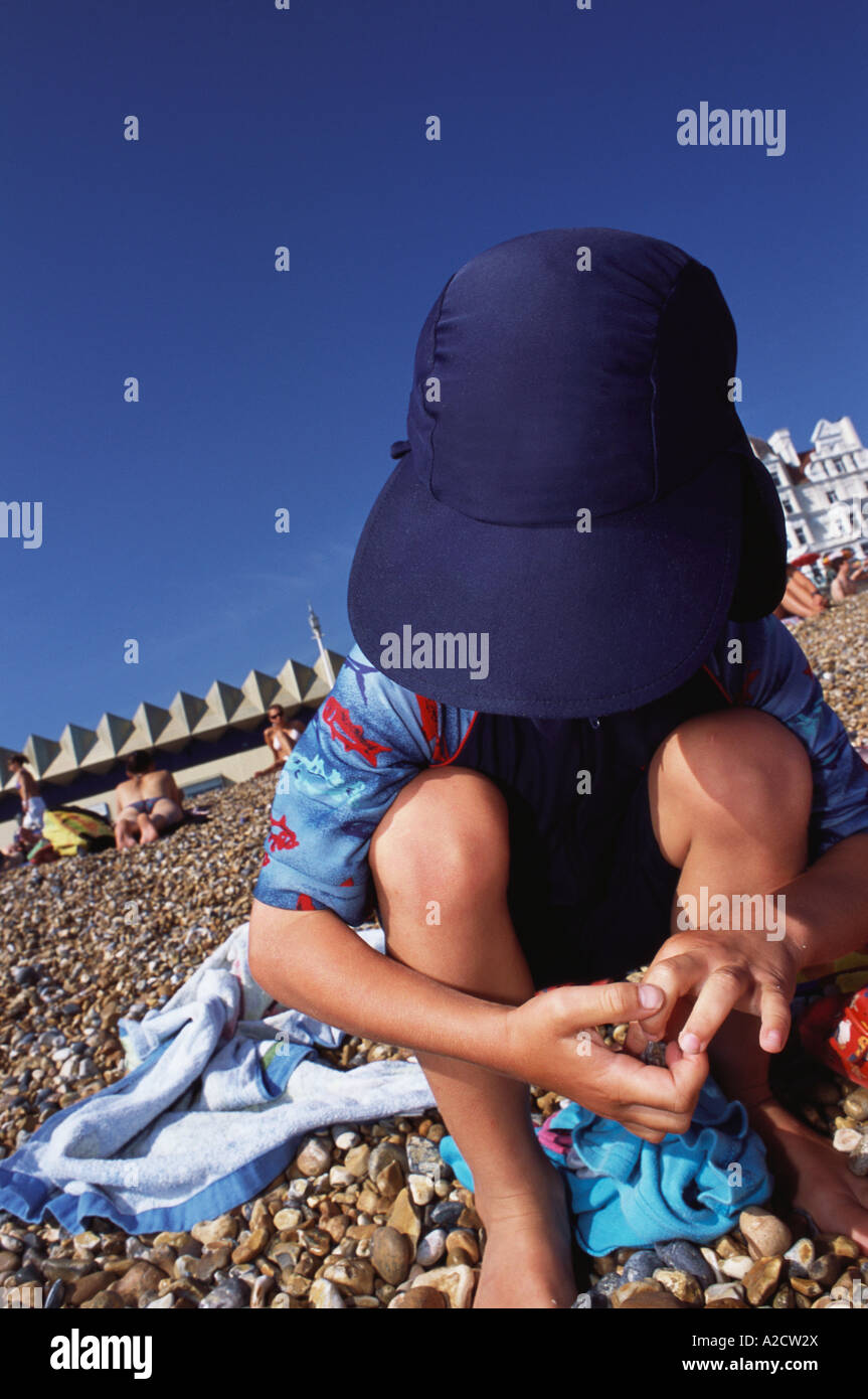 Six Year old boy plays with stones on Brighton Beach Sussex UK - Stock Image