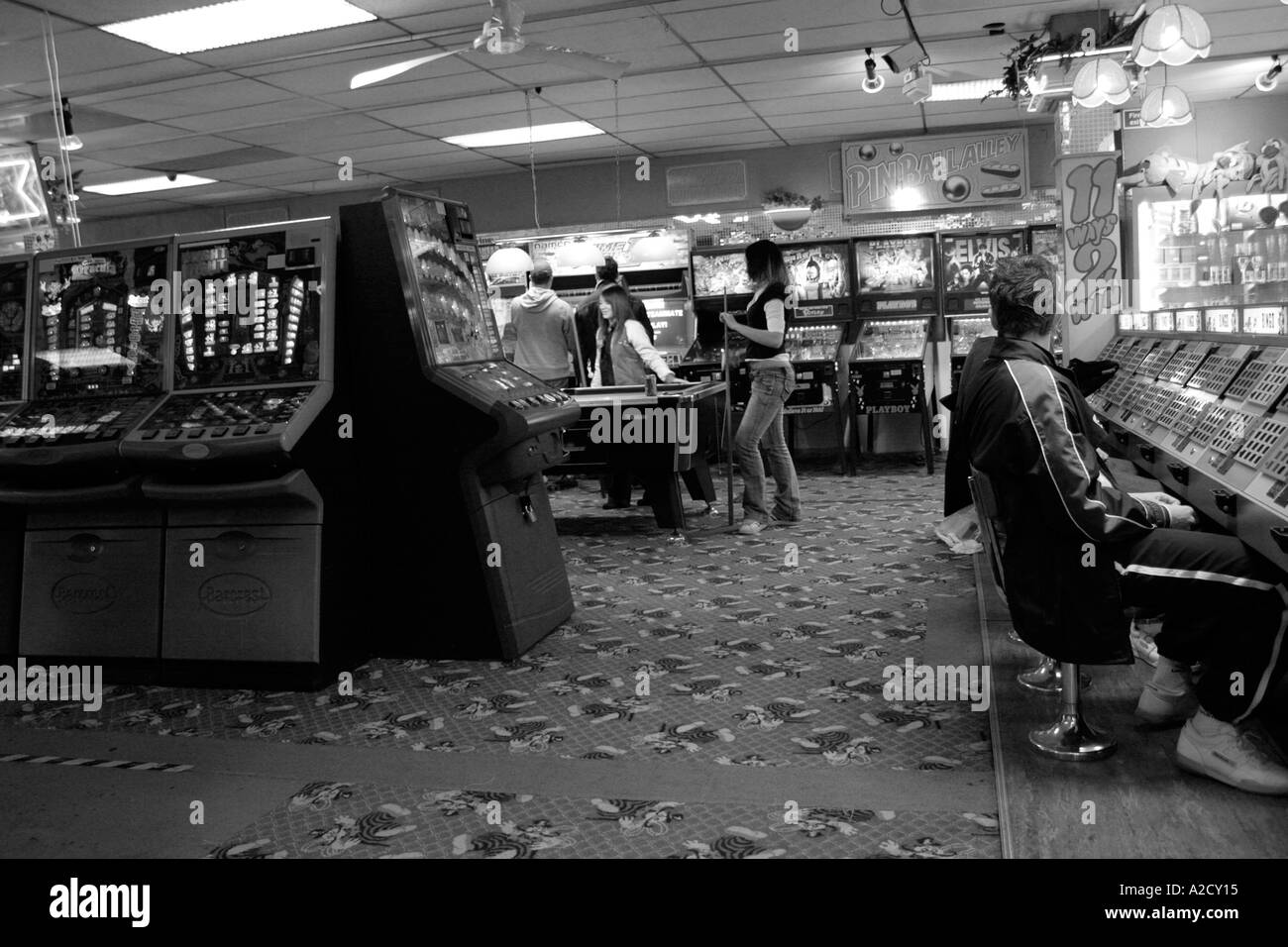 black and white image off an arcade with people playing the machines - Stock Image