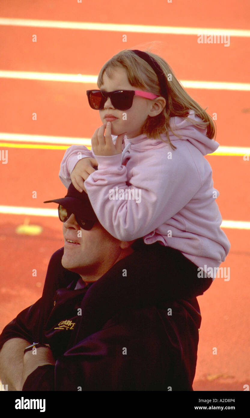 Thoughtful girl with sunglasses riding on dads shoulders at track meet age 28 and 5. St Paul Minnesota USA - Stock Image