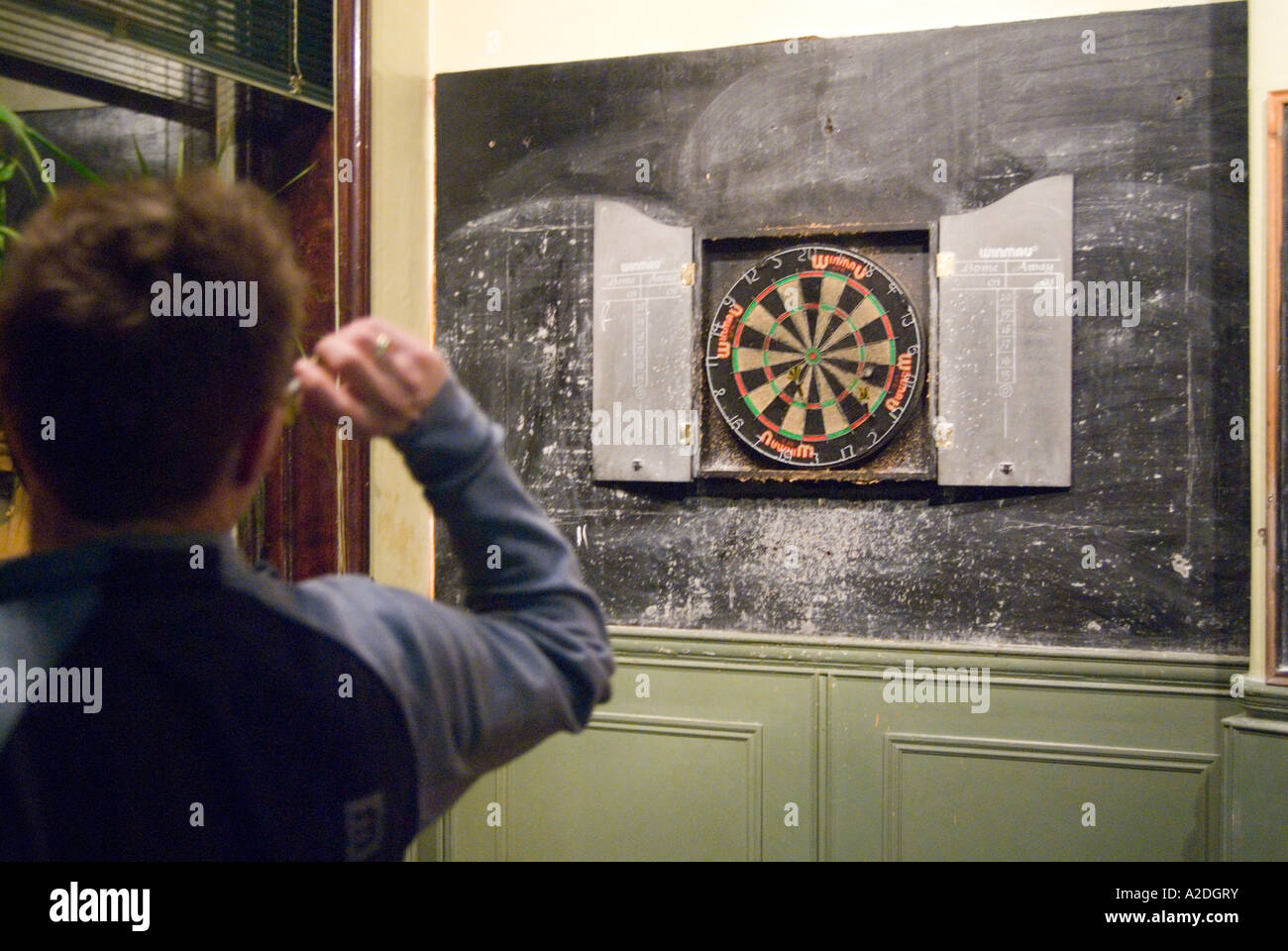 Man Playing Traditional Game Of Darts In Pub London England Uk