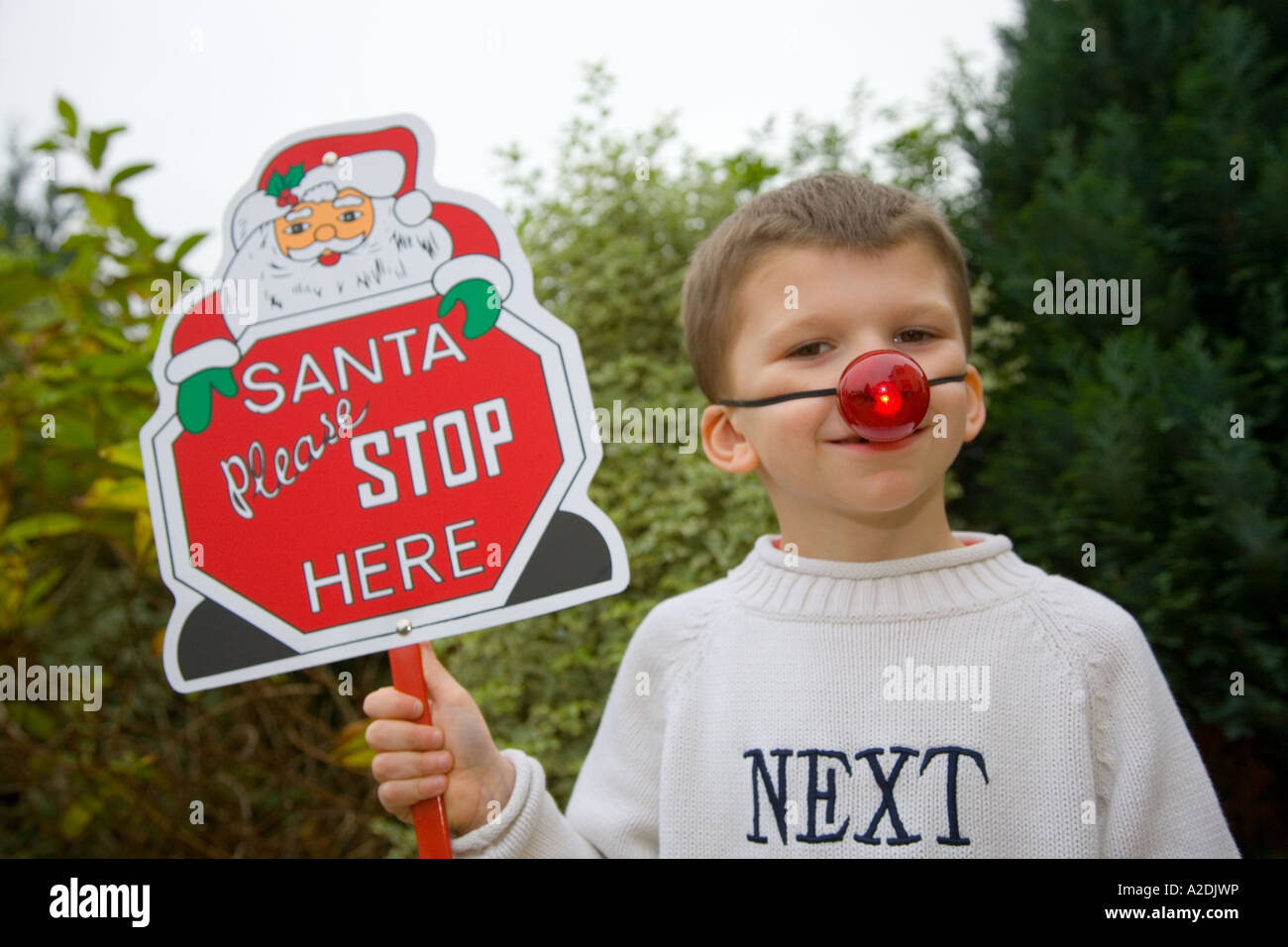 Young boy wearing next jumper holding placard ' Santa please Stop here' Stock Photo