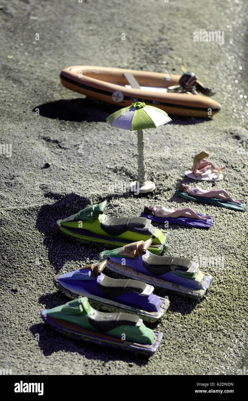 jetskis sunbathers beach scene black sand volcanic holiday concept rest recueration lesiure sunbathe lounge lie - Stock Image