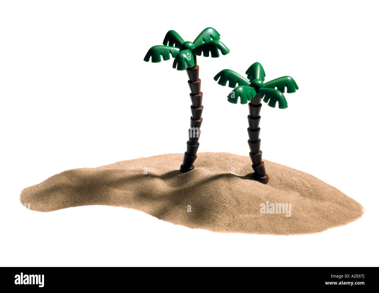 A sand desert island with two toy palm trees - Stock Image