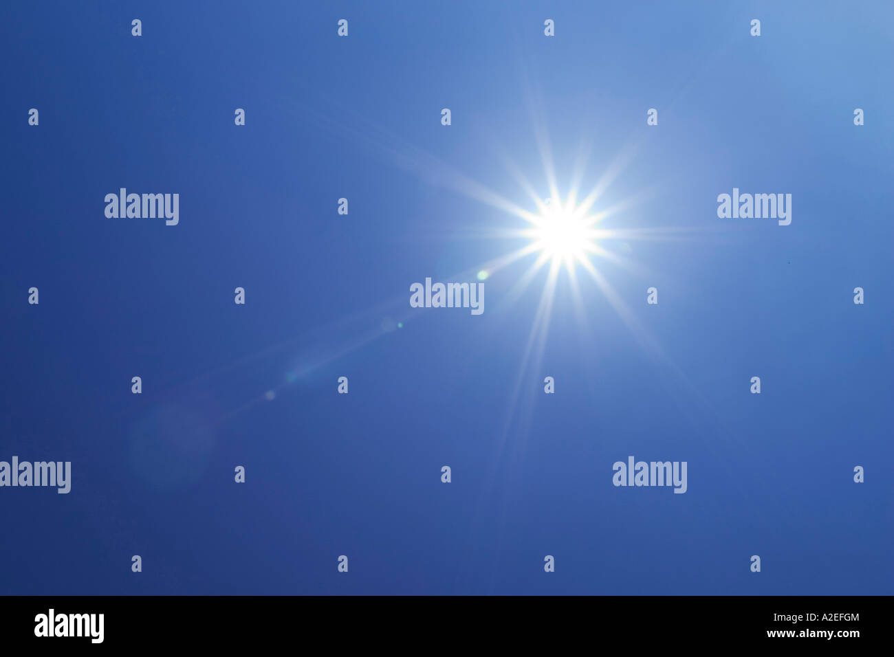 sun shining high in the sky with a corona or ring of rays - Stock Image