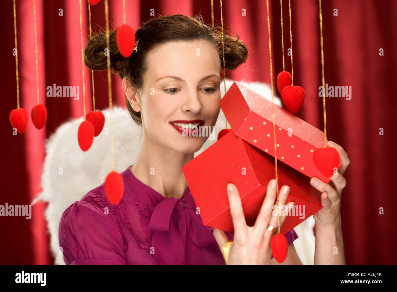 1219207 indoor studio young woman girl 20 35 brunette hairdo hairstyle purple blouse hold box red present open unpack - Stock Image