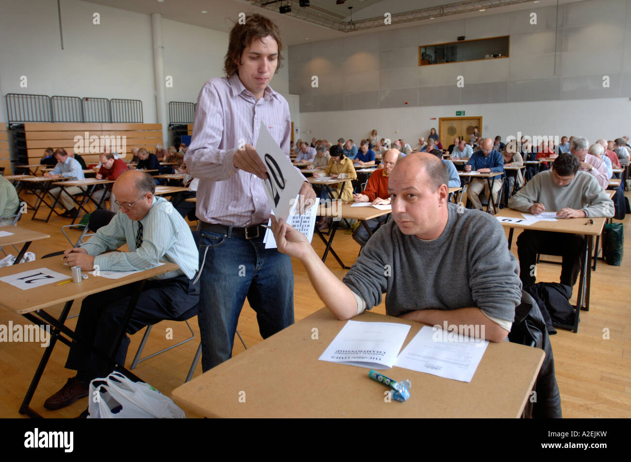 A CONTESTANT HANDS IN HIS FINISHED ENTRY AT THE TIMES NATIONAL CROSSWORD COMPETITION CUP DURING THE CHAMPIONSHIPS Stock Photo