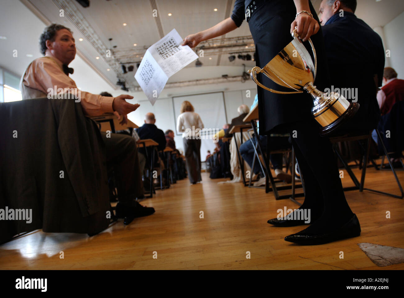 A CONTESTANT HANDS IN HIS FINISHED ENTRY AT THE TIMES NATIONAL CROSSWORD COMPETITION CUP Stock Photo