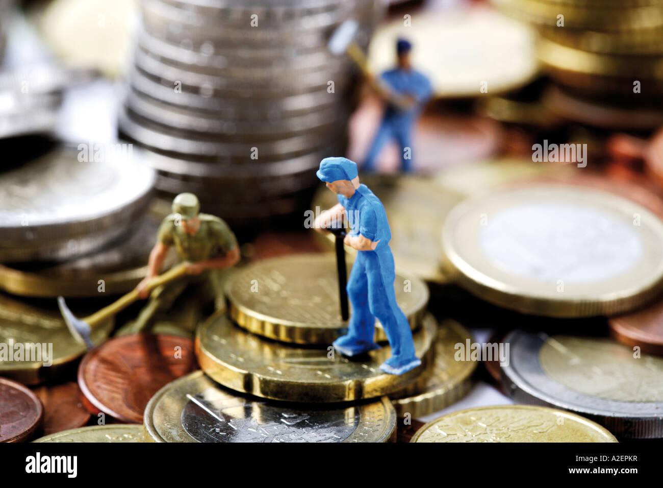 Figurines digging money Stock Photo