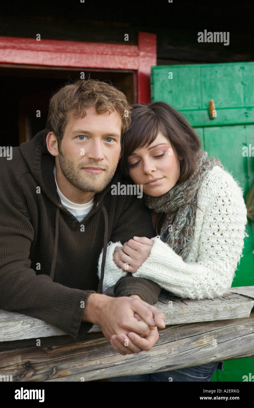 Young couple leaning on wooden rail in front of alpine hut - Stock Image