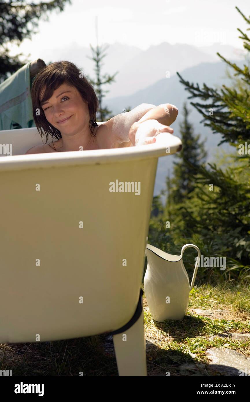 Young woman lying in bathtub - Stock Image