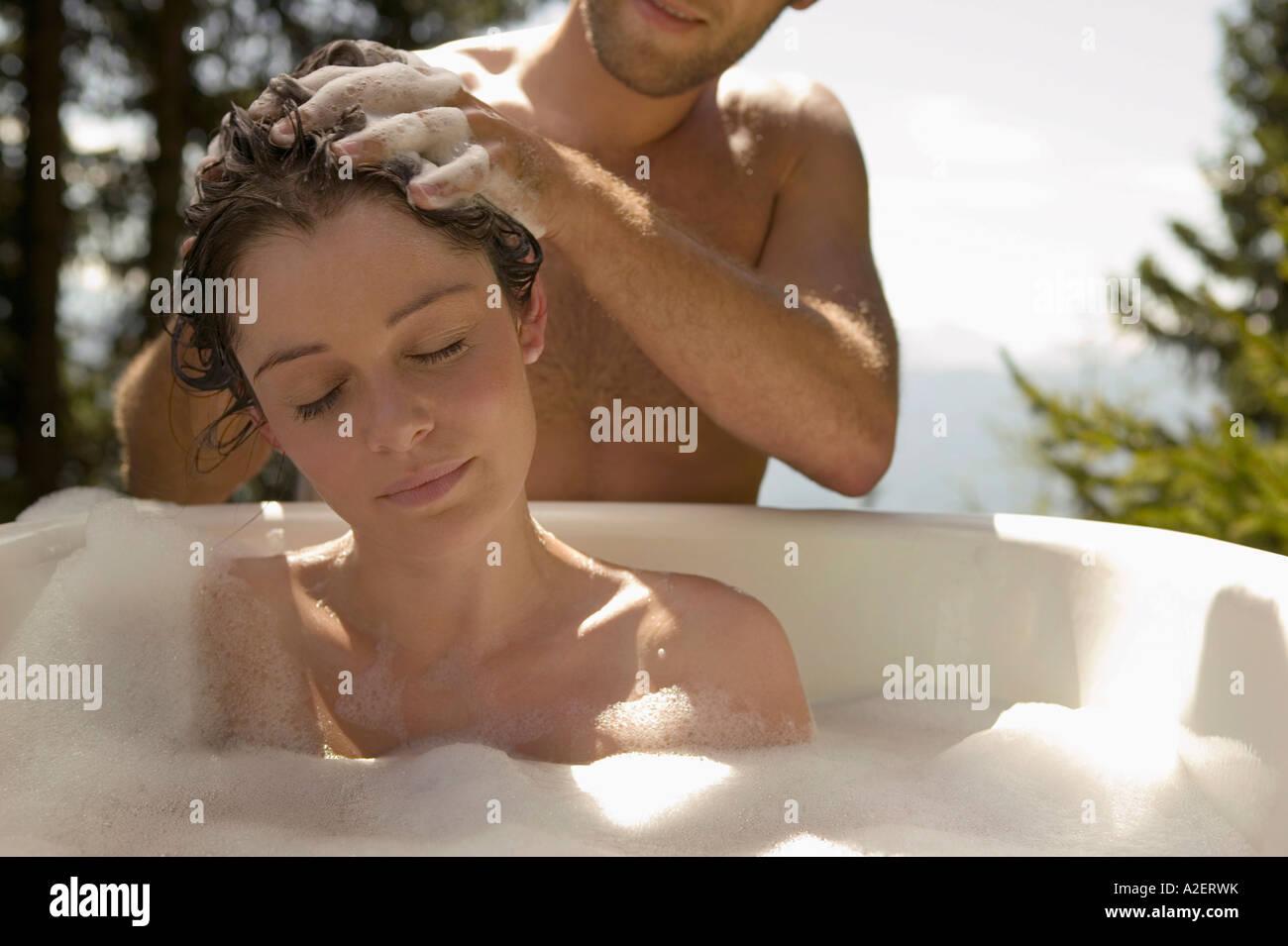Young woman lying in bathtub, young man washing hair - Stock Image