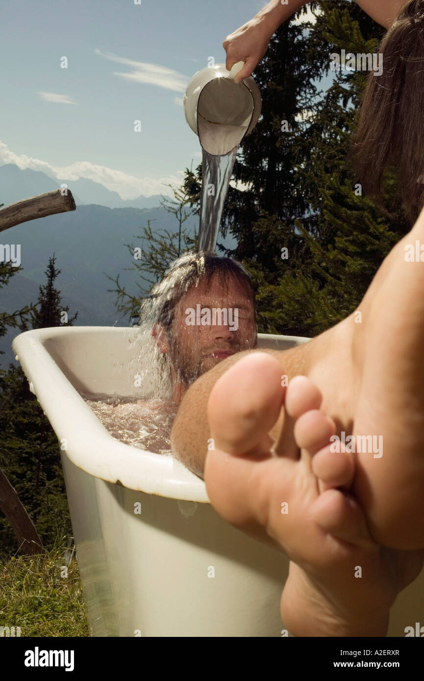 Young man lying in bathtub, young woman pouring water on man - Stock Image