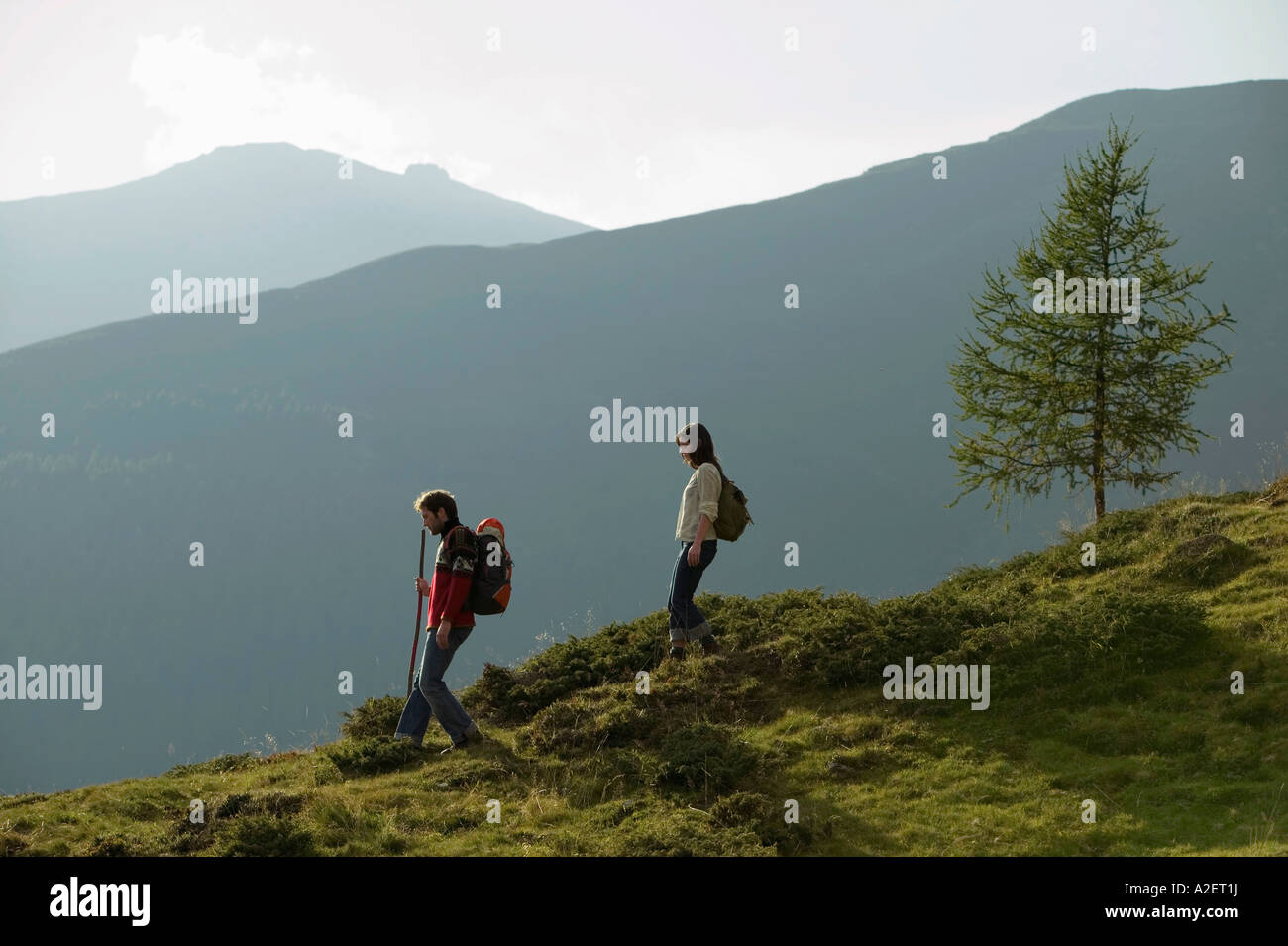 Young couple walking in mountains - Stock Image