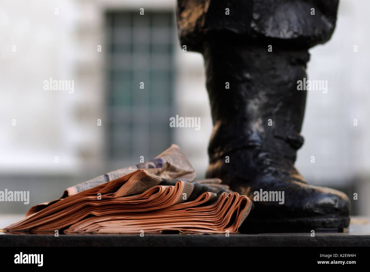 Foot of statue of general Smuts and a pile of newspapers in Whitehall London - Stock Image