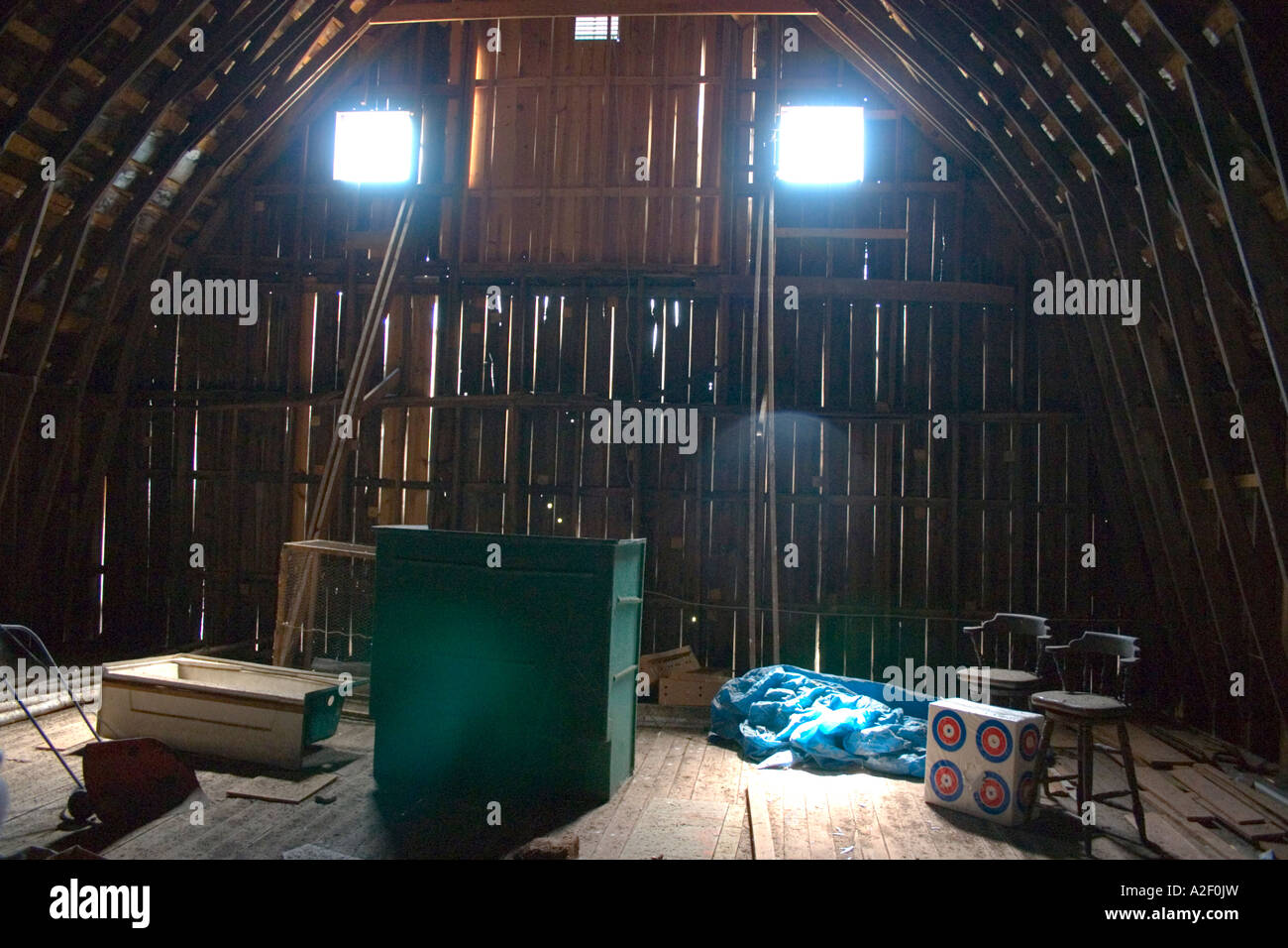 Bar chairs beside targets in barn attic. Blue River Wisconsin USA Stock Photo