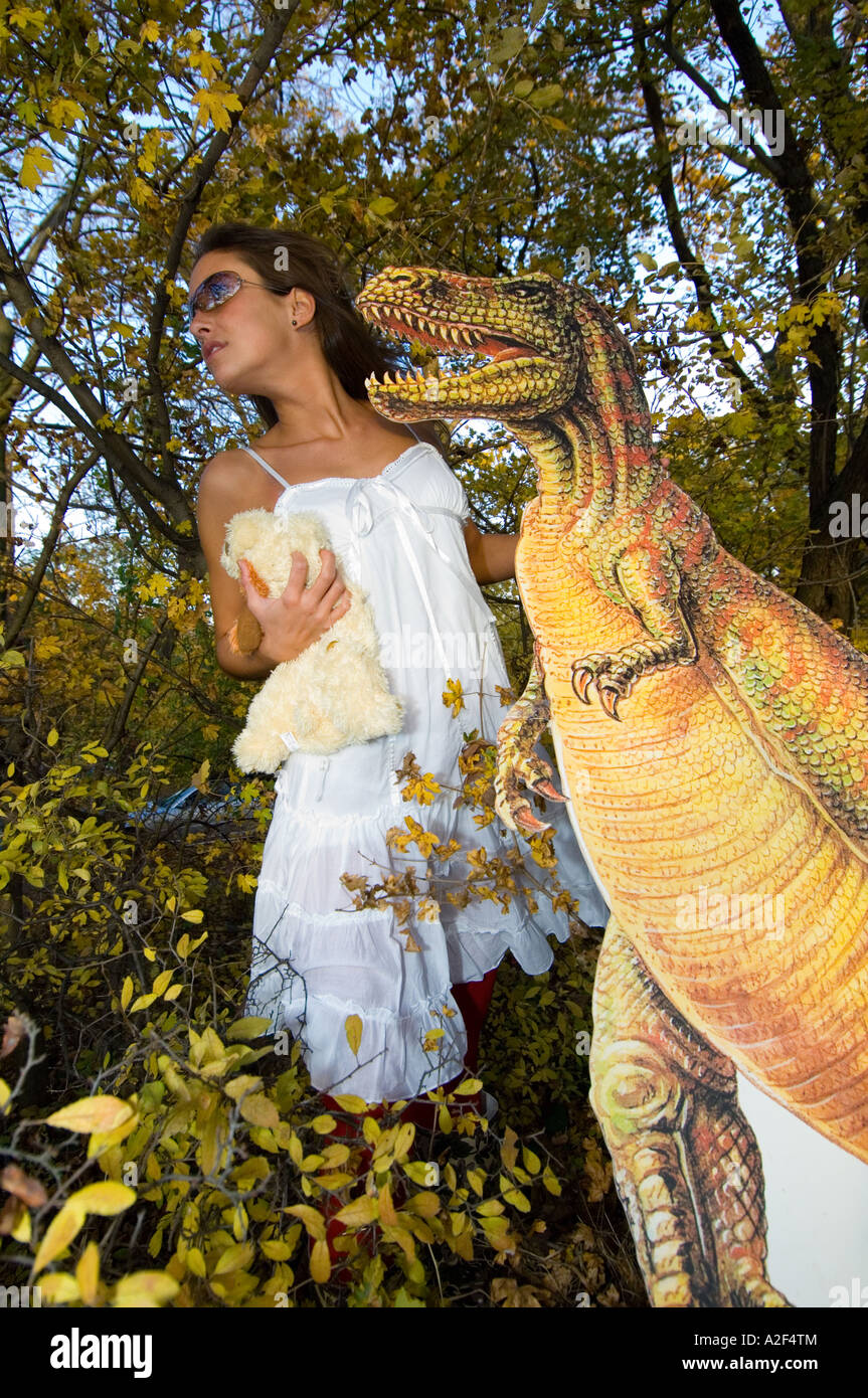 Young women with dinosaur in bushes - Stock Image