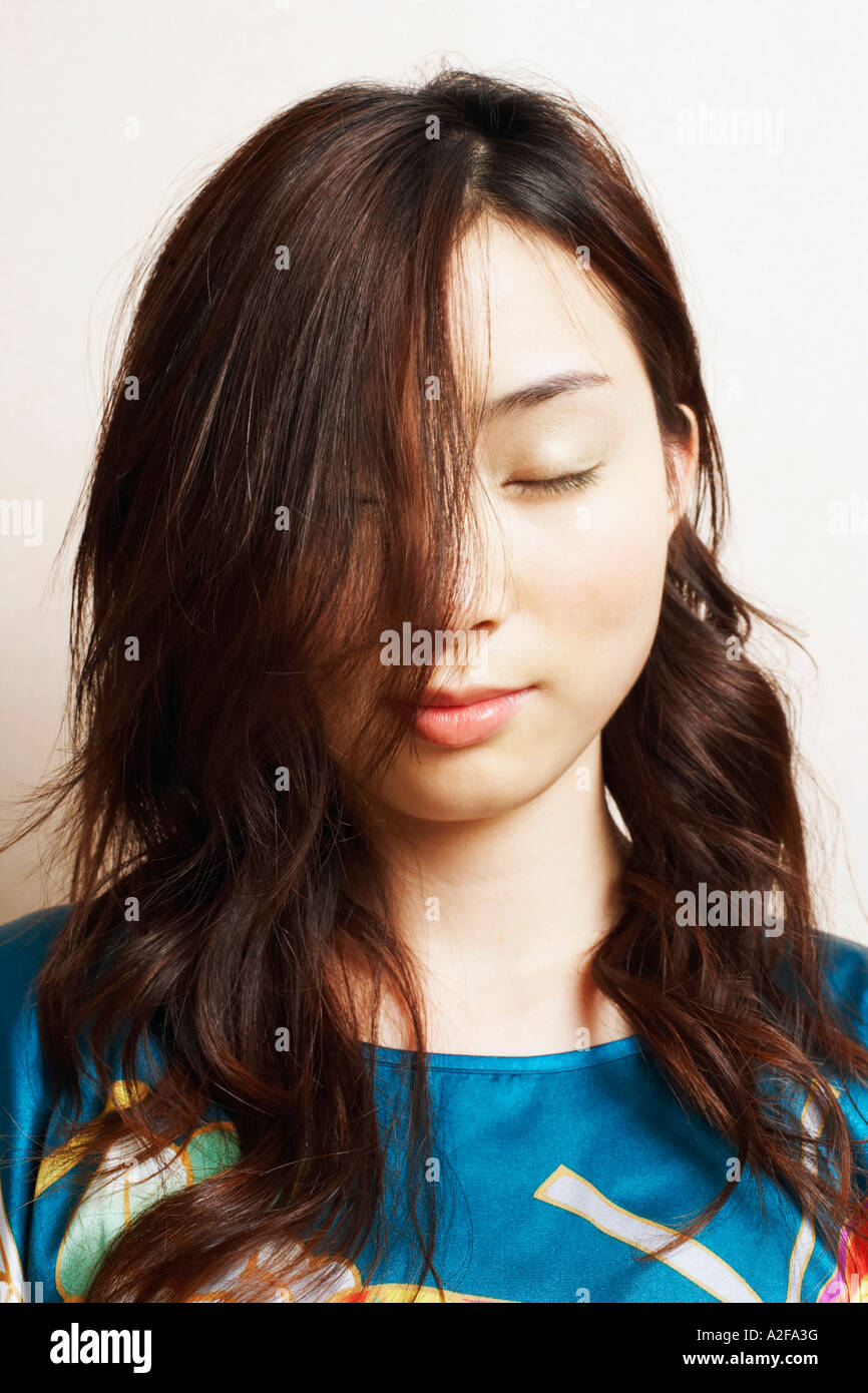 Close-up of a young woman with her eyes closed - Stock Image