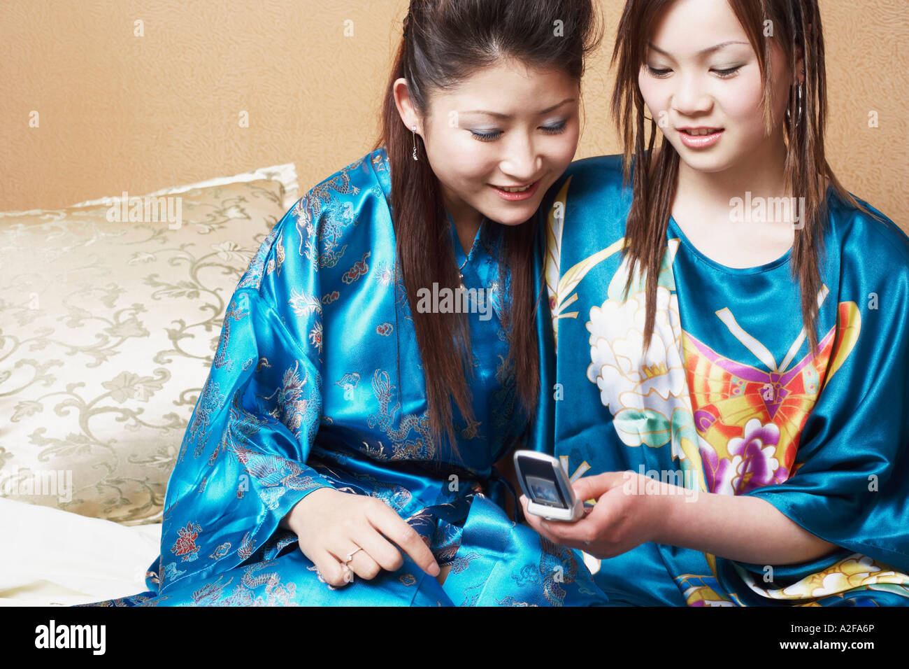 Close-up of a young woman sitting with a teenage girl looking at a mobile phone - Stock Image