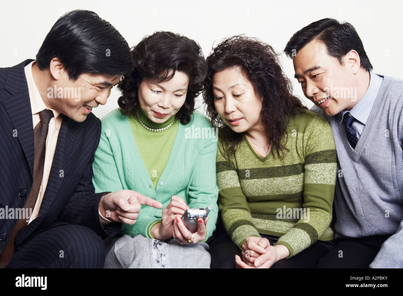 Close-up of two mature couples sitting together looking at a mobile phone Stock Photo