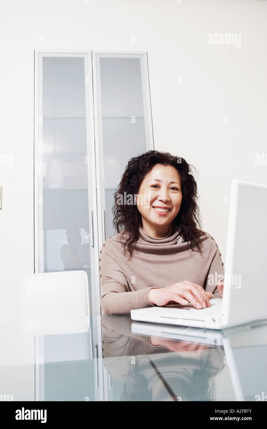 Portrait of a businesswoman using a laptop smiling - Stock Image