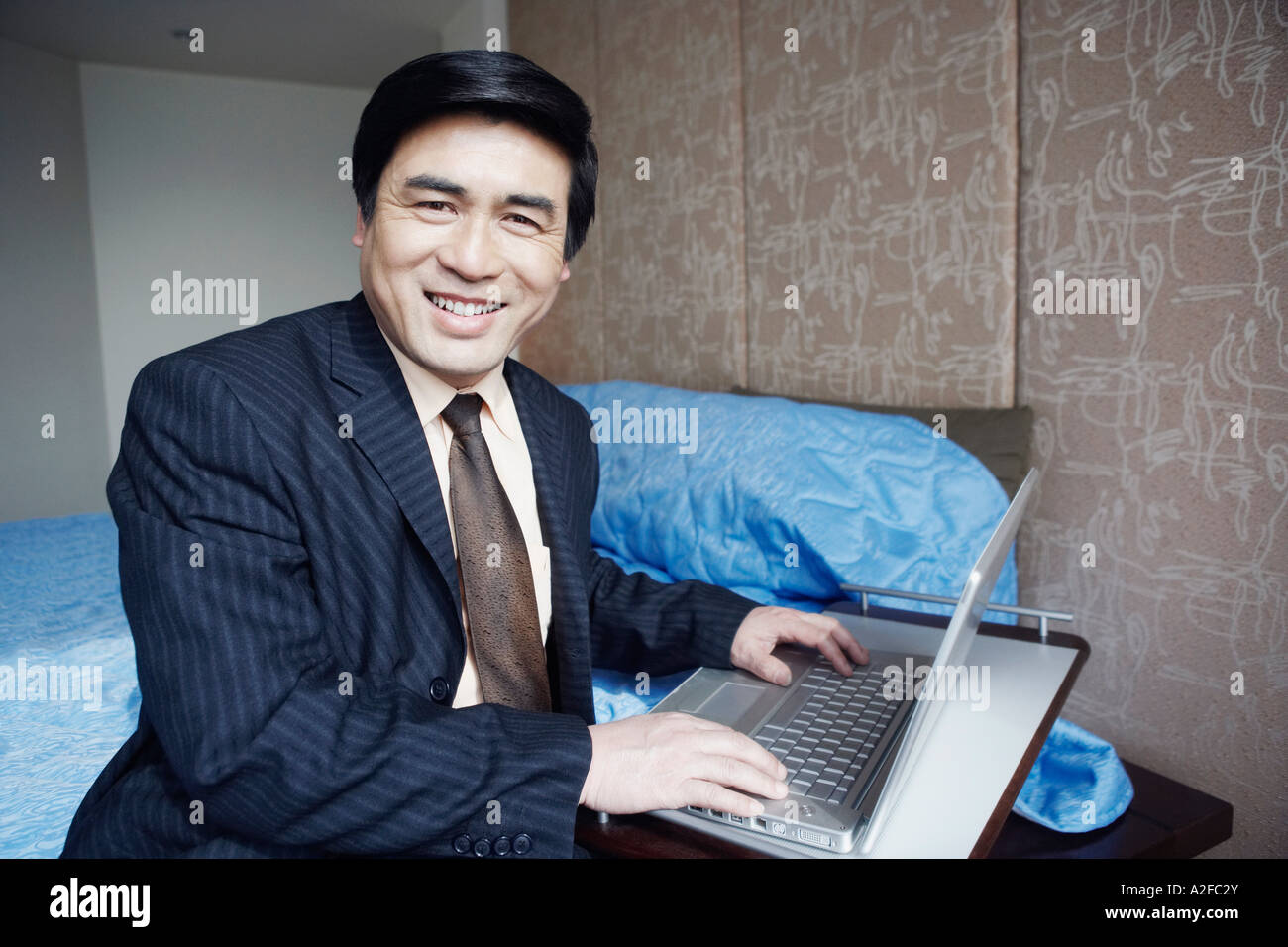 Portrait of a businessman sitting on the bed smiling - Stock Image