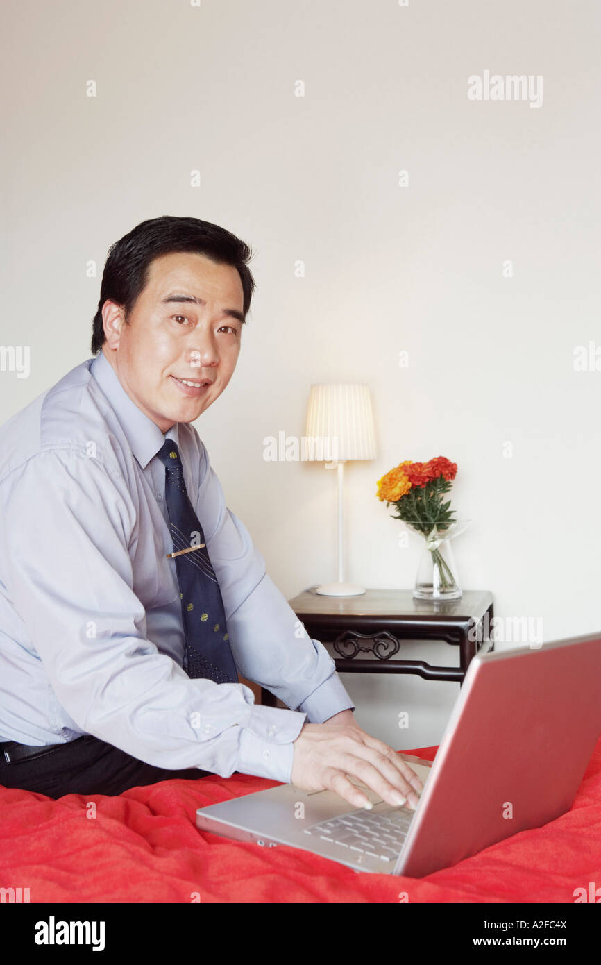 Portrait of a businessman sitting on the bed using a laptop - Stock Image