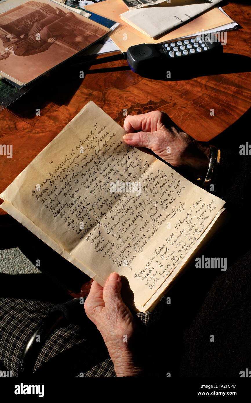The hands of an elderly person hold an old hand written letter with copperplate handwriting - Stock Image