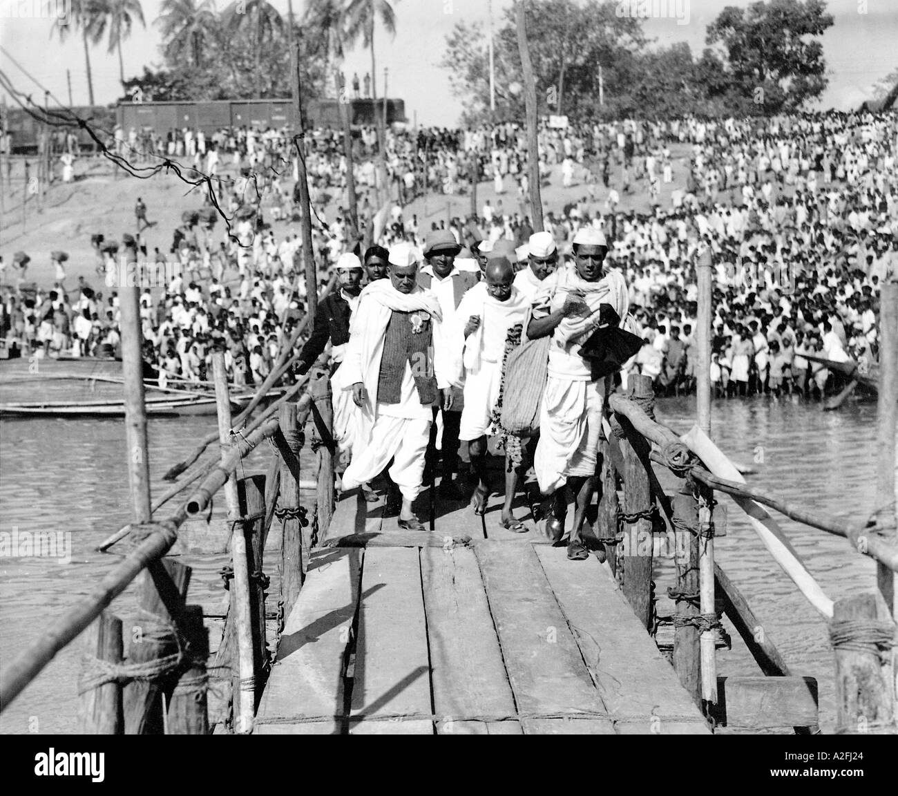 Mahatma Gandhi walking with stick on wooden bridge during his tour to Assam in North East India AsiaStock Photo