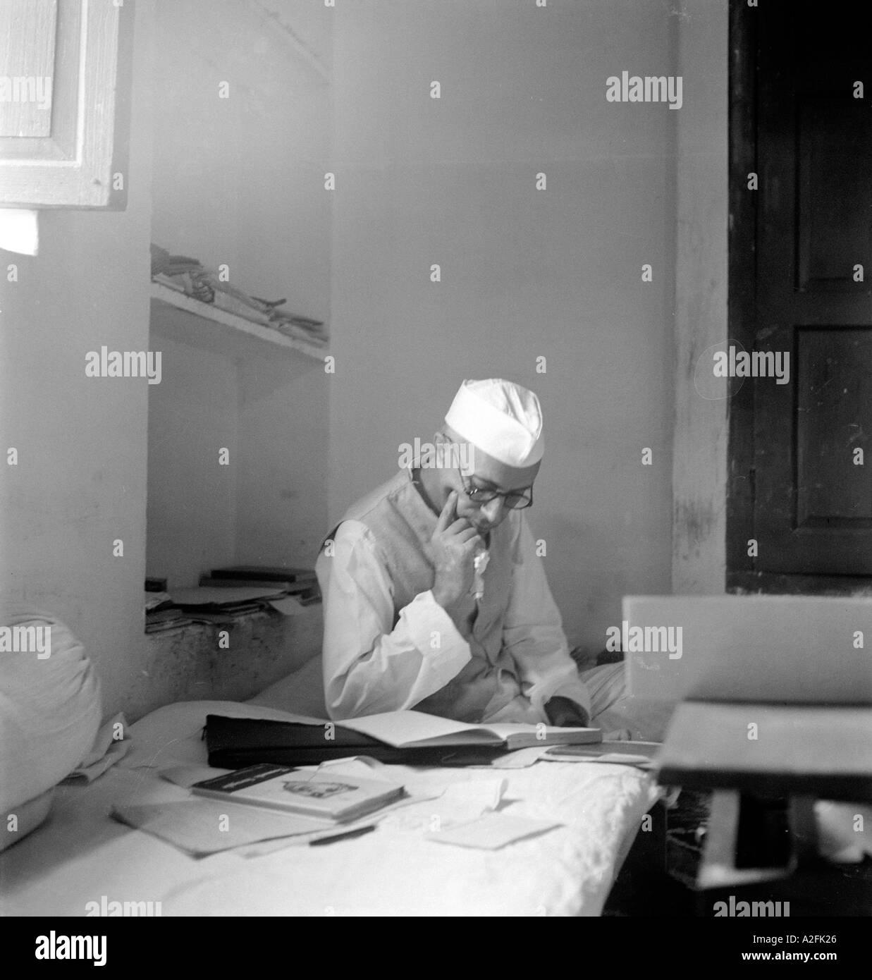Jawaharlal Nehru in jacket cap sitting thinking reading on mattress at Bhangi Sweepers Colony New Delhi India 2 October 1946 - Stock Image