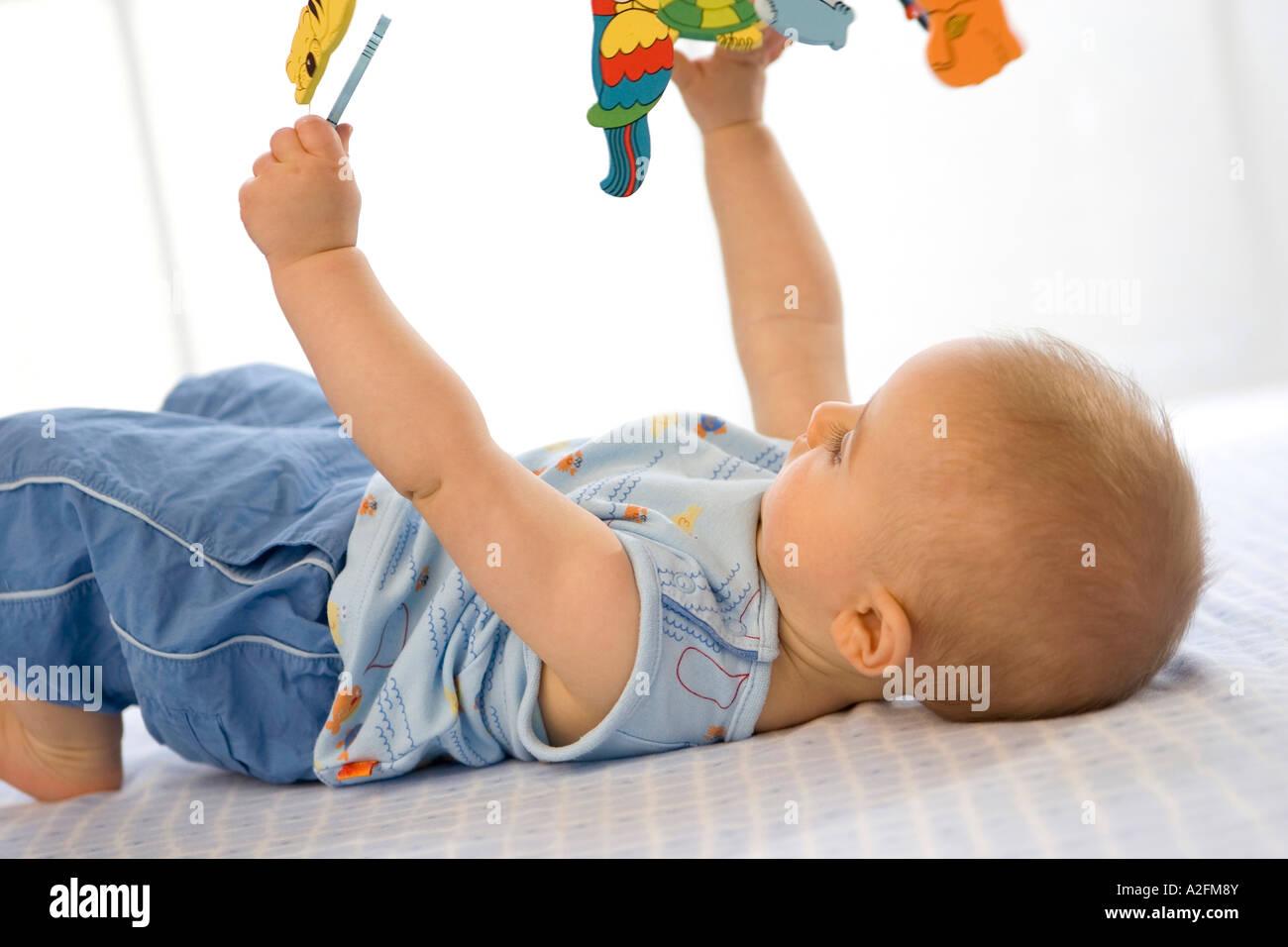 Baby Boy 6 12 Months Lying On Back Holding Toys Stock Photo