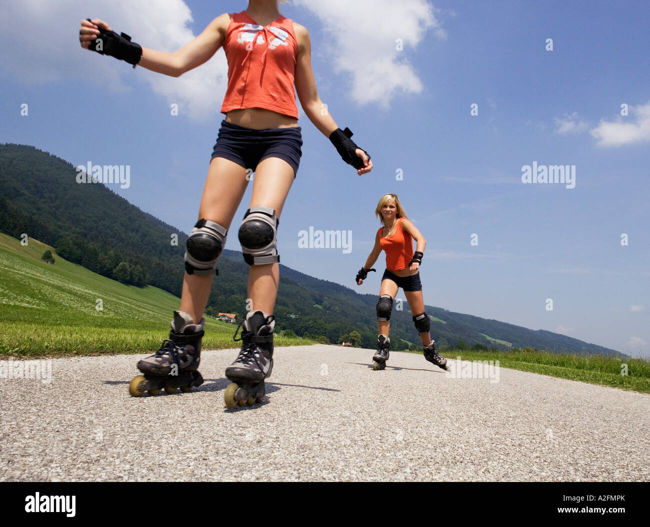 Two teenage girls (13-15) inline skating - Stock Image
