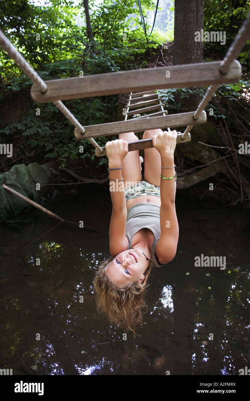 Teenage girl (13-15) hanging upside down on rope-ladder - Stock Image