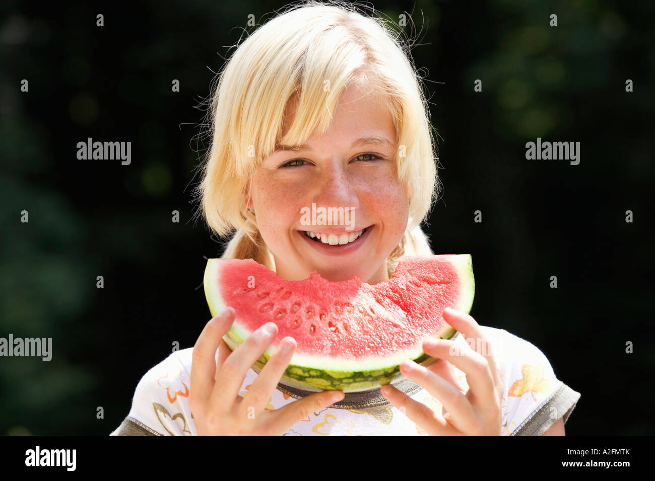 Teenage girl (13-15) eating watermelon, close-up, portrait - Stock Image